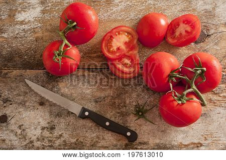 Preparing fresh tomatoes for a salad or cooking with an overhead view of ripe cherry tomatoes and a kitchen knife on an old chopping board