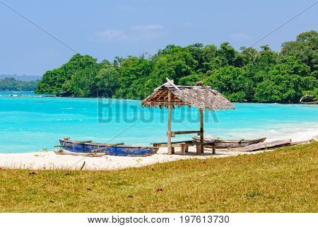 Outrigger canoes and a leaf beach bungalow at Olry Bay - Espiritu Santo, Vanuatu