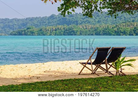 Deckchairs on the tranquil sandy beach at Velit Bay - Espiritu Santo, Vanuatu
