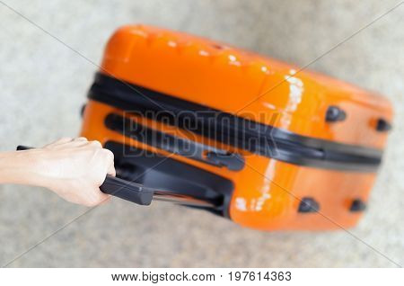 Woman Holds Orange Suitcase In Hand