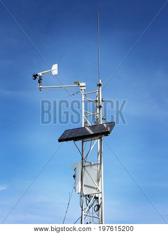 Scientific working weather station with solar panel on blue sky background