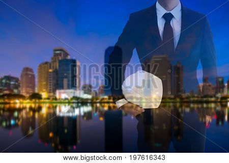 Double exposure Copy space for inscription engineer white helmet for workers security on the background city scape