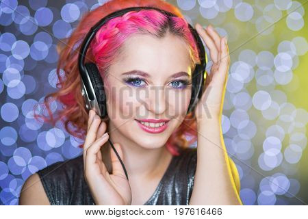 beauty woman isten to music in headphones on light ball bokeh background