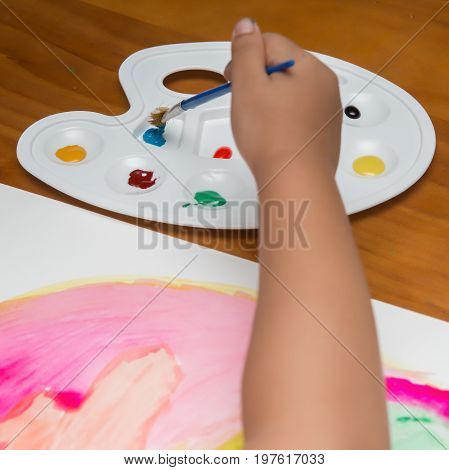 a little kid doing colorful painting square comp;osition