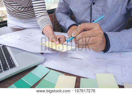 Two colleagues interior Creative creativity graphic designer working with graphics laptop blueprint and colour chart at workplace on wooden desk colour ideas style concept.