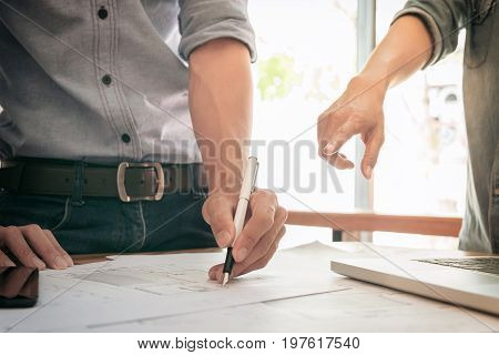 Image of engineer or architectural project engineering and partner drawing plan on Blue Print with Engineering tools on workplace.