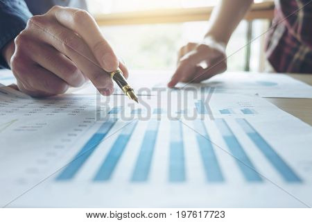 Two Business man or accountant working Financial investment writing report Analyze business and market growth and pointing on financial document data graph Accounting Economic commercial.