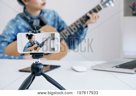 social media learning concept relaxing and playing guitar Young woman concentrating learn and play the guitar to a tutorial on lesson online while she recording music video in camera at home.