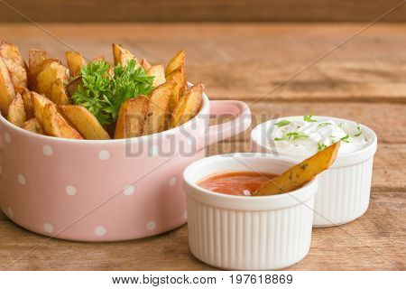 Homemade french fries serve with ketchup and sour cream or mayonnaise. Golden brown crispy french fries sprinkle with salt and oregano on bowl for snack or appetizer. Delicious french fries ready to served on wood table with dipping sauce.