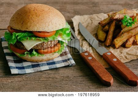 Homemade hamburger on plaid napkin with french fries. Delicious sandwich hamburger with meat or pork ham cheese and fresh vegetable. Hamburger or sandwich is the popular fast food for brunch or lunch. Cheese burger ready to served on table.