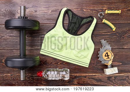 Sport equipment, prize, wooden background. Heavy physical training and succes in sports.