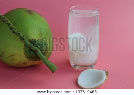 Fresh  coconut water in glass Ready to drink on  pink background, summer and healthy concept.