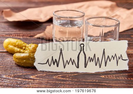 Vodka in transparent glass shots. Vodka in glass shots, pickle cucumbers, image of heart impulses on wooden table. Concept of alcoholism.