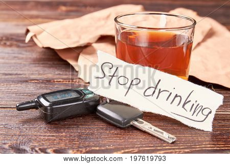 Automobile keys, message, glass of alcohol. Message stop drinking, car keys, glass of alcohol beverage. Stop drinking and obey the law.