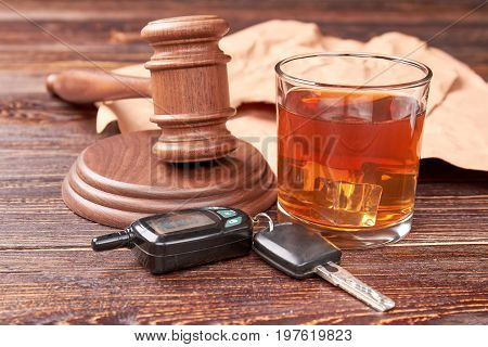 Drunk driving concept. Driving keys, gavel, glass of whisky on wooden background. Drink and drive is hard crime.
