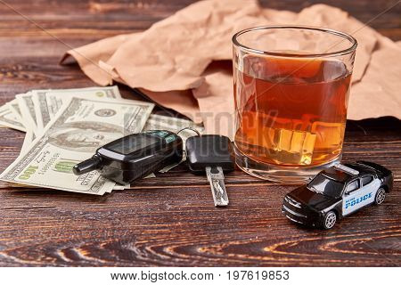 Dollars, keys, whiskey, police car. Glass of whiskey beside of car keys and police car. Money penalty for alcohol drinking.