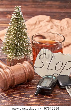 Glass of whiskey, wooden background. Automobile key, gavel, new year tree, note, paper. Stop drink when drive concept.