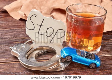 Pair of handcuffs, car, whiskey. Glass of alcohol beside metal handcuffs on wooden background close up.