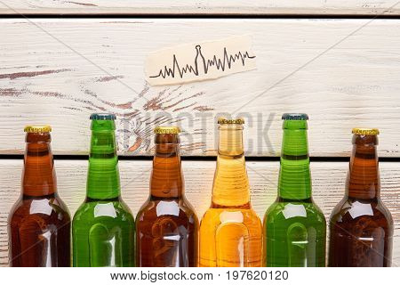 Heart problems from alcohol usage. Image of cardiac impulses, bottles with alcohol on old wooden background.