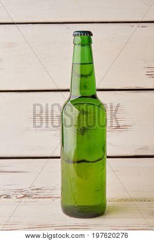 Full bottle of beer, old background. Single beer bottle, vertical image.