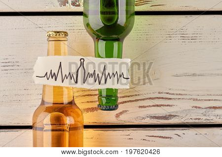 Alcohol harms your heart. Two full bottles, message, old wooden background.