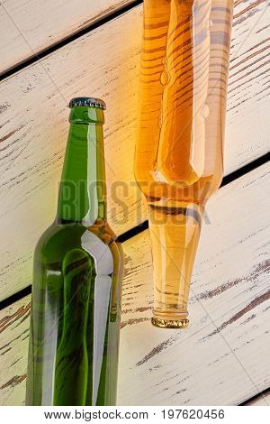 Bottles with beer close up. Cold light liquid, old retro boards.