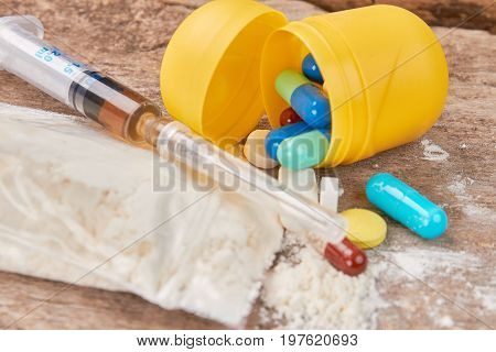 Narcotics on old wooden background. How get rid of drugs addiction.