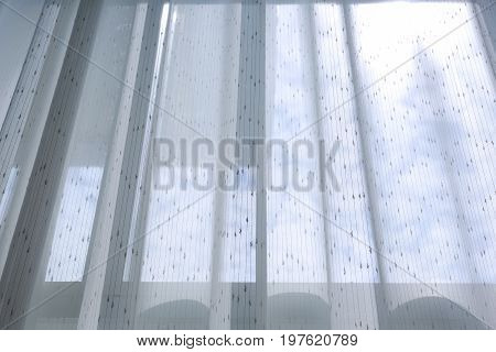 interior decoration home white drapery curtain hanging on the window with sun light in the morning day