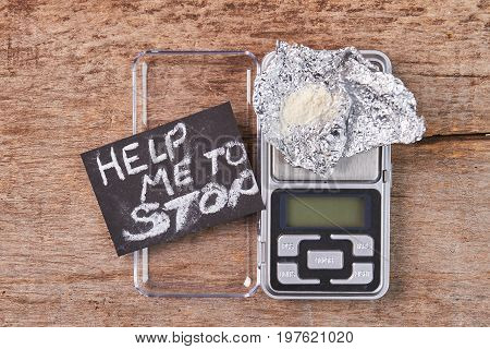 Treatment from drugs addiction. Message, digital scales, narcotics, wooden background.
