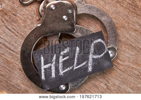 Handcuffs and message close up. Prisoner metal shackles, wooden background. Request of help.