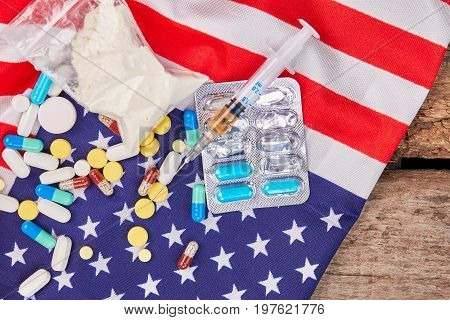 Drugs lie on American national flag. Syringe, pills, packet with powder, flag of America, wooden board.