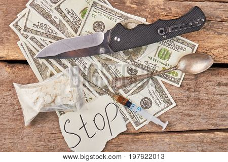Hard drugs, american money, knife. Message, amount of money, syringe, spoon, knife, wooden background. Narcotics addiction concept.