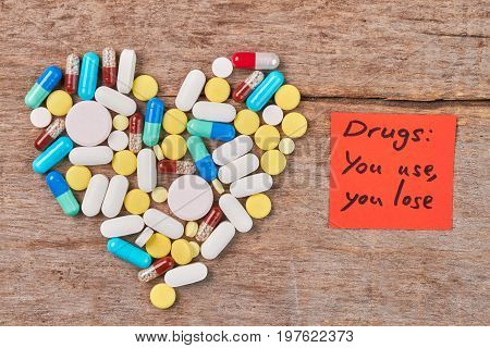 Drugs: you use, you lose. Colorful pills shaped heart, paper message, wooden table.