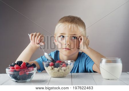 Sad child does not want to eat porridge with berries. Little boy eats without appetite. The concept of a healthy breakfast for children porridge with raspberries and blackberries a glass of yogurt.