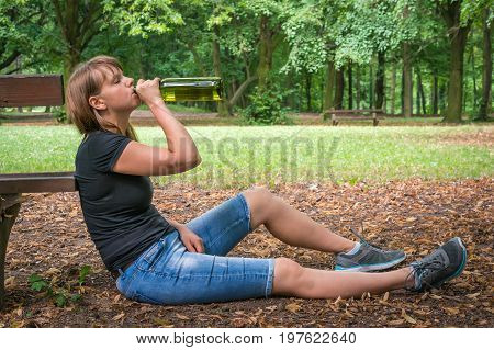 Lonely Drunken Woman Holding A Wine Bottle In The Park