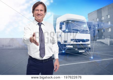 Mature man stretching out hand for shaking and truck on background. Wholesale and logistic concept