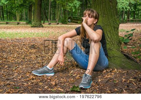 Woman Drinking Wine In The Park And Sitting Under Tree