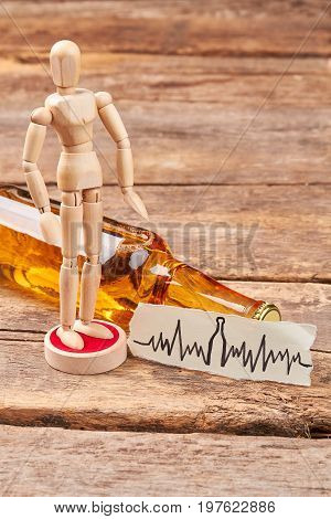 Human wooden dummy standing near alcohol. Wooden human figure, bottle of alcohol, wooden background. Alcohol harm health.