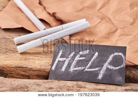Help to overcome cigarette addiction. Text help, white tobacco cigarettes, burnt paper sheet, old wooden background.