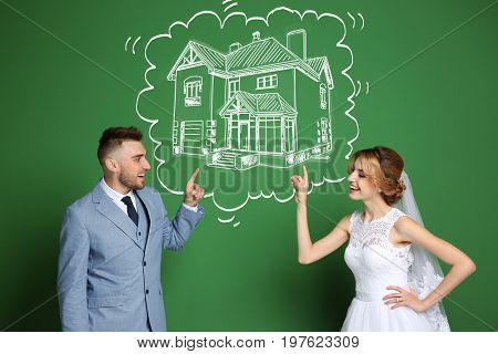 Happy wedding couple dreaming about house and drawing on color background
