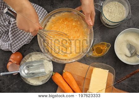 Woman making dough for carrot cake on kitchen table