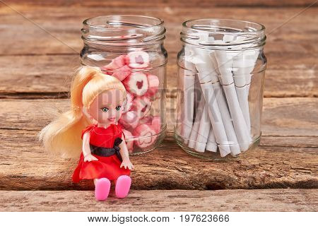Toy doll sitting near jars. Jars with sweets and tobacco cigarettes, little doll, wooden background.