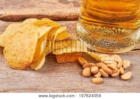 Chips, peanuts, beer close up. Mug of beer, unhealthy food on old wooden background.