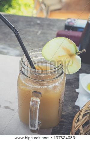 Close up of cold and fresh made apple juice in cafe of Bali island. Healthy drink in the glass. Sweet, delicious diet drink concept.