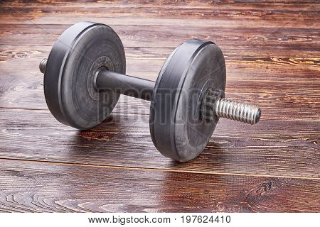 Single black dumbblle isolated. Heavy dumbbell for weightlifting on wooden background. poster