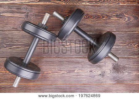 Two black dumbbells, top view. Heavy objects for lifting in gym on wooden background.