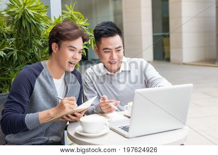 Two attractive mature students talking and working outdoors on laptop