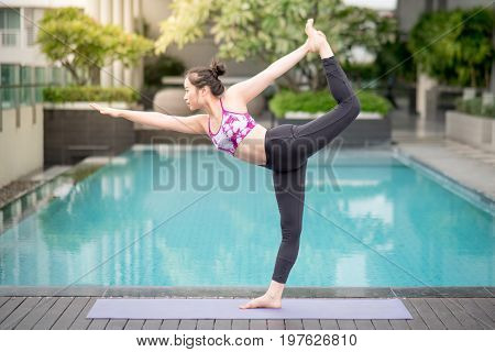 Beautiful young Asian woman doing yoga exercise with Natarajasana posing (Lord of the dance pose) near swimming pool. Healthy lifestyle and good wellness concepts