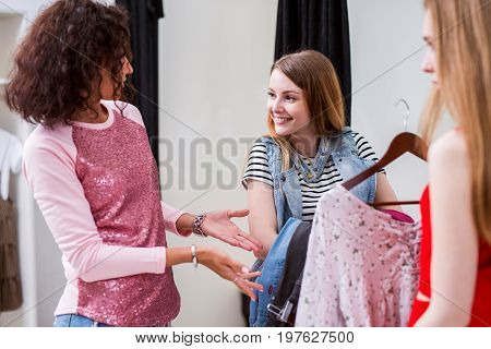Shy smiling girl holding a pack of clothes listening to fashion stylist helping her picking outfit in a changing room.