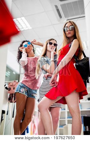 Women trying new ladies summer collection of clothes and accessories looking in mirror in clothing store.